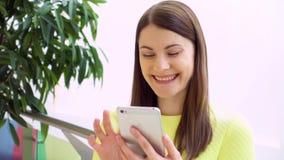 Mujer hermosa joven que se coloca en la alameda de compras que sonríe en la cámara lenta Usando la charla del smartphone almacen de video