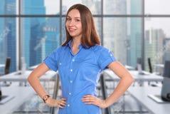 Mujer hermosa joven que se coloca en la oficina Imagenes de archivo