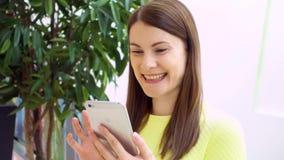 Mujer hermosa joven que se coloca en la sonrisa de la alameda de compras Usando su smartphone, charlando con los amigos almacen de video