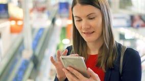 Mujer hermosa joven que se coloca en la sonrisa de la alameda de compras Usando su smartphone, hablando con los amigos almacen de video