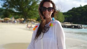 Mujer hermosa joven que se divierte en la costa tropical Muchacha feliz que camina en la playa tropical de la arena blanca almacen de video
