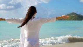 Mujer hermosa joven que se divierte en la costa tropical Muchacha feliz que camina en la playa tropical de la arena blanca Cámara metrajes
