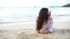 Mujer hermosa joven que se divierte en la costa tropical Muchacha feliz que miente en la playa tropical de la arena blanca almacen de metraje de vídeo