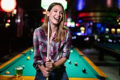 Mujer hermosa joven que se divierte y que juega el billar en un club fotos de archivo