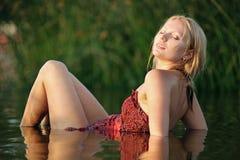 Mujer hermosa joven que se reclina en agua Fotos de archivo