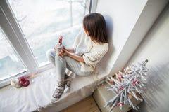 Mujer hermosa joven que se relaja con café caliente en travesaño de la ventana adentro Fotografía de archivo