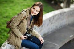Mujer hermosa joven que se sienta en banco en parque Viajero con la cámara del vintage Imagenes de archivo