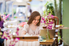 Mujer hermosa joven que se sienta en café Foto de archivo libre de regalías