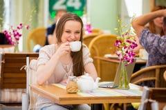 Mujer hermosa joven que se sienta en café Fotos de archivo libres de regalías