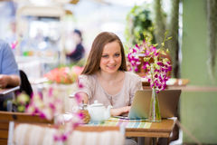 Mujer hermosa joven que se sienta en café Fotografía de archivo libre de regalías