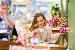Mujer hermosa joven que se sienta en café Foto de archivo