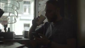 Mujer hermosa joven que se sienta en café cerca de la ventana y que usa el smartphone, practicando surf Internet, café de consumi metrajes