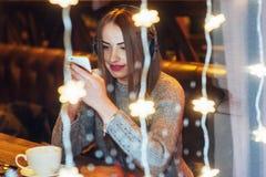 Mujer hermosa joven que se sienta en el café, café de consumición El escuchar modelo la música La Navidad, Año Nuevo, día de tarj Fotos de archivo libres de regalías