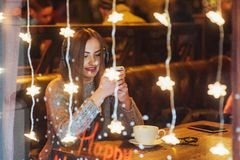 Mujer hermosa joven que se sienta en el café, café de consumición El escuchar modelo la música La Navidad, Año Nuevo, día de tarj Fotografía de archivo