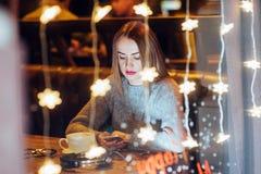 Mujer hermosa joven que se sienta en el café, café de consumición La Navidad, Año Nuevo, día de tarjetas del día de San Valentín, Fotografía de archivo