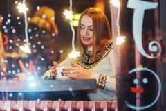 Mujer hermosa joven que se sienta en el café, café de consumición La Navidad, Año Nuevo, día de tarjetas del día de San Valentín, Foto de archivo libre de regalías