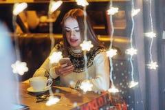 Mujer hermosa joven que se sienta en el café, café de consumición La Navidad, Año Nuevo, día de tarjetas del día de San Valentín, Imagen de archivo