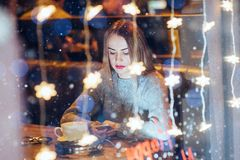 Mujer hermosa joven que se sienta en el café, café de consumición La Navidad, Año Nuevo, día de tarjetas del día de San Valentín, Imagen de archivo libre de regalías