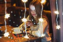 Mujer hermosa joven que se sienta en el café, café de consumición La Navidad, Año Nuevo, día de tarjetas del día de San Valentín, Imagenes de archivo
