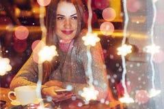 Mujer hermosa joven que se sienta en el café, café de consumición La Navidad, Año Nuevo, día de tarjetas del día de San Valentín, Fotos de archivo libres de regalías