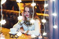 Mujer hermosa joven que se sienta en el café, café de consumición La Navidad, Año Nuevo, día de tarjetas del día de San Valentín, Fotografía de archivo libre de regalías