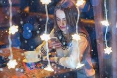 Mujer hermosa joven que se sienta en el café, café de consumición La Navidad, Año Nuevo, día de tarjetas del día de San Valentín, Imágenes de archivo libres de regalías