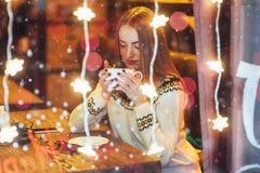 Mujer hermosa joven que se sienta en el café, café de consumición La Navidad, Año Nuevo, día de tarjetas del día de San Valentín, Foto de archivo