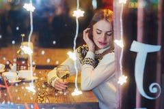 Mujer hermosa joven que se sienta en el café, vino de consumición La Navidad, Año Nuevo, día de tarjetas del día de San Valentín, Fotografía de archivo