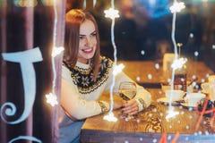 Mujer hermosa joven que se sienta en el café, vino de consumición La Navidad, Año Nuevo, día de tarjetas del día de San Valentín, Foto de archivo