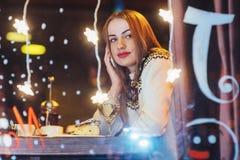 Mujer hermosa joven que se sienta en el café, vino de consumición La Navidad, Año Nuevo, día de tarjetas del día de San Valentín, Imagenes de archivo
