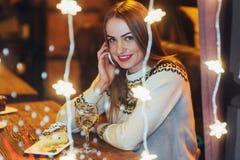 Mujer hermosa joven que se sienta en el café, vino de consumición La Navidad, Año Nuevo, día de tarjetas del día de San Valentín, Fotos de archivo