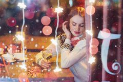 Mujer hermosa joven que se sienta en el café, vino de consumición La Navidad, Año Nuevo, día de tarjetas del día de San Valentín, Fotos de archivo libres de regalías