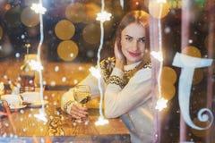 Mujer hermosa joven que se sienta en el café, vino de consumición La Navidad, Año Nuevo, día de tarjetas del día de San Valentín, Imágenes de archivo libres de regalías