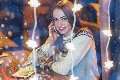 Mujer hermosa joven que se sienta en el café, vino de consumición La Navidad, Año Nuevo, día de tarjetas del día de San Valentín, Foto de archivo libre de regalías