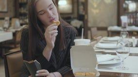 Mujer hermosa joven que se sienta en el restaurante costoso y que come las pepitas de pollo con la Coca-Cola almacen de metraje de vídeo