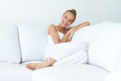Mujer hermosa joven que se sienta en el sofá fotos de archivo libres de regalías
