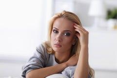 Mujer hermosa joven que se sienta en el sofá en su sitio Fotos de archivo