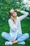 Mujer hermosa joven que se sienta en hierba en parque de la ciudad del verano y Imágenes de archivo libres de regalías