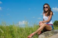 Mujer hermosa joven que se sienta en hierba verde en copyspace del fondo del cielo azul Foto de archivo libre de regalías
