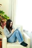 Mujer hermosa joven que se sienta en la butaca con la tableta Foto de archivo libre de regalías