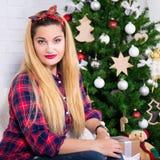 Mujer hermosa joven que se sienta en sitio adornado con la Navidad t Foto de archivo libre de regalías