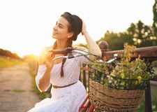 Mujer hermosa joven que se sienta en su bicicleta con las flores en el sol Fotografía de archivo