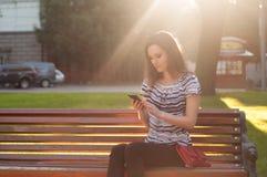 Mujer hermosa joven que se sienta en un banco y que mecanografía un mensaje encendido fotos de archivo