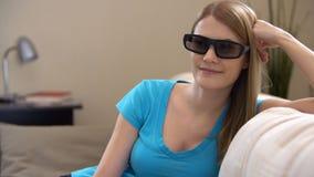 Mujer hermosa joven que se sienta en un sofá en 3d-glasses Interruptores en película elegante de la TV y de los relojes 3d almacen de video