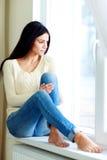 Mujer hermosa joven que se sienta en un ventana-travesaño Fotos de archivo libres de regalías