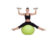 Mujer hermosa joven que se sienta en una bola gimnástica con pesas de gimnasia Foto de archivo libre de regalías
