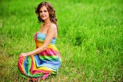 Mujer hermosa joven que se sienta encendido Foto de archivo libre de regalías