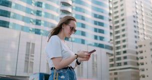 Mujer hermosa joven que sonríe con smartphone a disposición contra rascacielos del verano metrajes