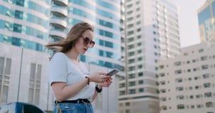 Mujer hermosa joven que sonr?e con smartphone a disposici?n contra rascacielos del verano almacen de metraje de vídeo