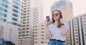 Mujer hermosa joven que sonr?e con smartphone a disposici?n contra rascacielos del verano almacen de video